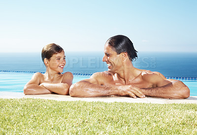 Buy stock photo Portrait of a smiling father and son leaning in the water pool and lokking at each other