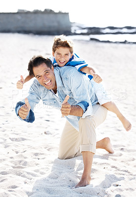 Buy stock photo Portrait of a happy father carrying his son on back and both showing thumbs up at the beach