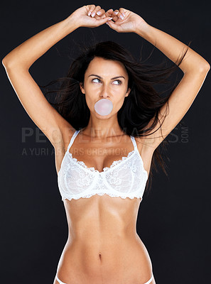 Buy stock photo Portrait of a sensual young woman blowing bubble gum in lingerie against grunge background
