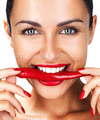 Buy stock photo Closeup portrait of a happy young woman holding red hot chilli in mouth