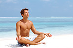 Relaxed young man meditating on the beach