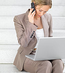 Young beautiful business woman using her cell phone and working on computer