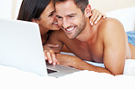 Happy couple relax in bed with laptop