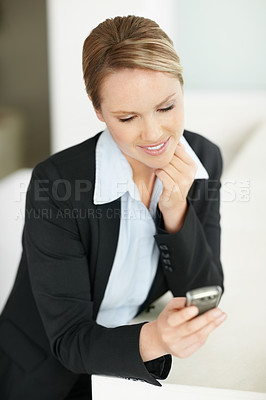 Young business woman reading message on mobile phone