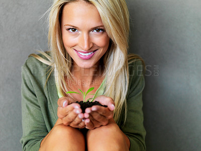 Buy stock photo Portrait of a beautiful happy young woman holding a small plant