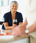 Smiling old woman having wine while husband preparing food