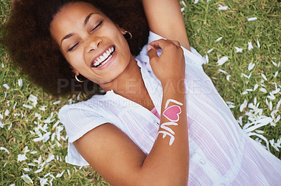 Buy stock photo Laughing African American female with a love written on her arm lying on grass