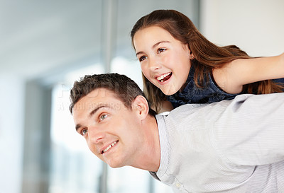 Happy middle aged man giving piggyback ride to a playful girl