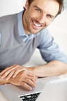 Closeup of happy middle aged man with a laptop