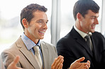Business men applauding during a meeting in the office.