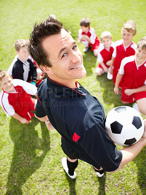 Buy stock photo Rear-view portrait of a soccer coach holding a ball with his team in the background