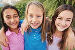 Smiling three girls standing together outdoors