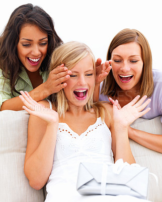 Young women with a happy surprised girl looking at a gift