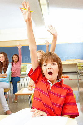 Smiling boy raising hand in classroom with colleagues in background