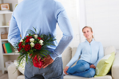 Buy stock photo Young man hiding flowers before a beautiful woman