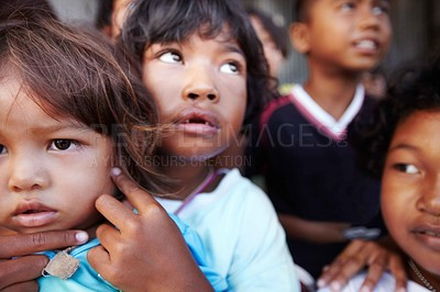 Buy stock photo An Thai toddler sitting on the lap of his older brother, with other children in the background