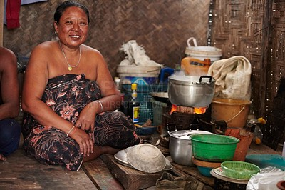 Buy stock photo A middle-aged Thai woman cooks a meal on the floor in her makeshift kitchen