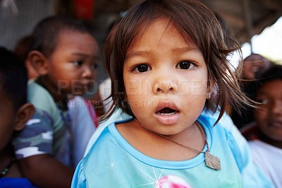 Buy stock photo A Thai toddler staring at the camera with other children in the background
