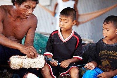 Buy stock photo Portrait of a fisherman in Thailand teaching his children his work