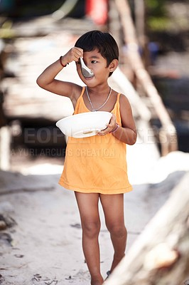 Buy stock photo Portrait of a little kid from rural Thailand enjoying food while walking
