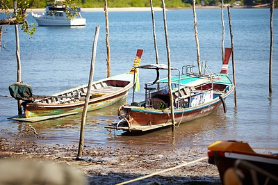 Buy stock photo Portrait of two fishing boats docked on the shores of the river in rural Thailand