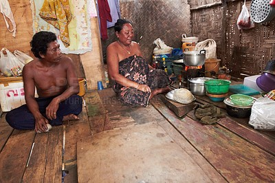 Buy stock photo A native man and woman sitting and looking at the food being cooked