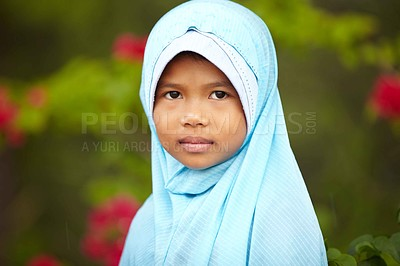 Buy stock photo A shy-looking girl wearing a blue headscarf
