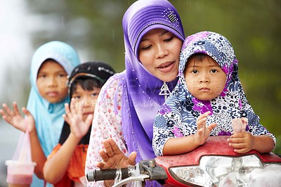 Buy stock photo A native mother trying to steer a scooter with one daughter sitting in front and two at the back