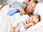 Happy family waking up in the morning on bed