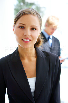 Buy stock photo Portrait of a young businesswoman standing outside with a colleague in the background