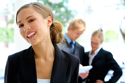 Buy stock photo Portrait of a young businesswoman standing outside with her colleagues in the background