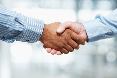 Buy stock photo Cropped closeup of a handshake between business partners, against a blurred background