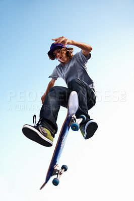 Buy stock photo A teenage boy doing a trick on his skateboard