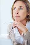 Mature woman holding her glasses daydreaming