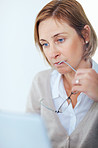 Business woman holding glasses in mouth thinking while working