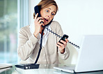 Woman with serious expression talking on both a cell phone and l