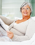 Relaxed senior woman reading newspaper on bed at home