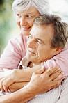 Closeup of a smiling senior woman with arms around a man