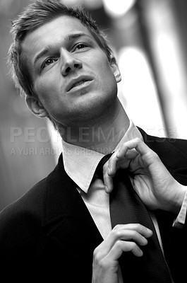 Buy stock photo Black-and-white portrait of a handsome young businessman straightening his tie