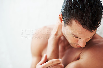 Buy stock photo Closeup of handsome young man looking down with hands on shoulder - copyspace