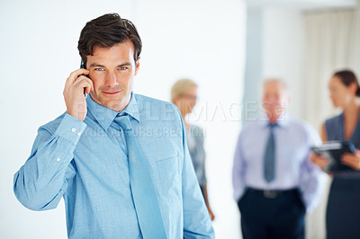 Buy stock photo Portrait of young handsome business man talking on cellphone with colleagues in background