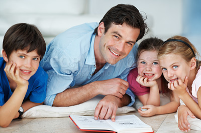 Buy stock photo Portrait of handsome man lying on the floor with his kids reading a book together