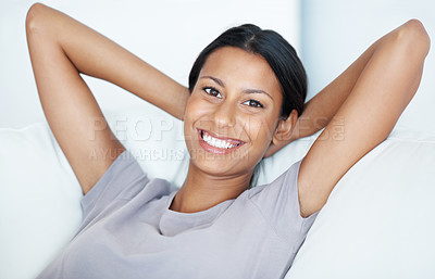 Buy stock photo Closeup of attractive mixed race woman smiling while relaxing on couch