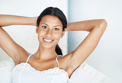 Buy stock photo Portrait of smiling mixed race woman relaxing on couch at home