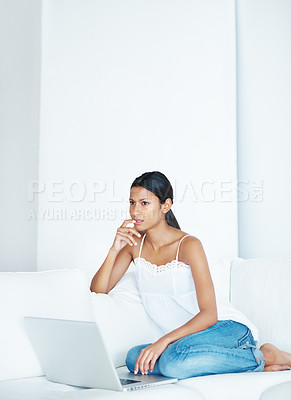 Buy stock photo Attractive mixed race woman thinking while using laptop on couch