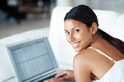 Buy stock photo Casually dressed mixed race woman using laptop while lying on couch