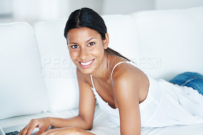Buy stock photo Charming mixed race woman using laptop while resting on couch