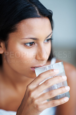 Buy stock photo Closeup of thoughtful mixed race woman drinking water