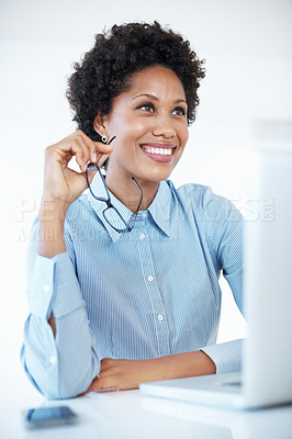 Buy stock photo Thoughtful business woman holding glasses while using laptop at work
