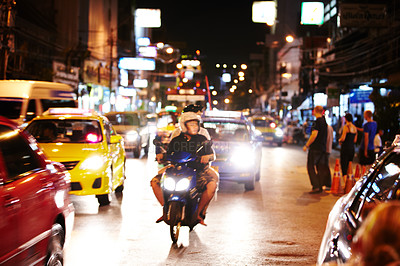 Buy stock photo Scooter traveling amidst heavy traffic in Bangkok at night